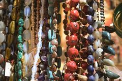 Stone beads. Beads of different multicolor semiprecious stones (lapis lazuli, malachite, turquoise, coral,  charoite)  in a souvenir shop. Landscape orientation Stock Photography