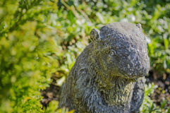 Stone beaver among garden plants Royalty Free Stock Photography