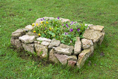 The stone bed with flowers Stock Photos