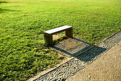 Stone bench. On grass land royalty free stock image