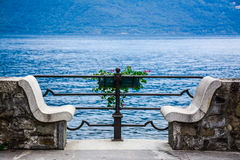 Stone bench. Beautiful stone bench for two on a lake in Italy Stock Photography