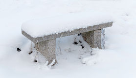 Stone bench covered with snow Royalty Free Stock Photo