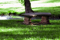 Stone Bench by Creek. Peaceful scene of a stone bench in the shade beside a small creek in lush green grass royalty free stock photography