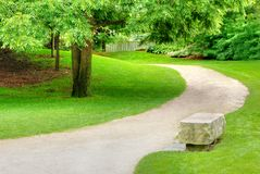 Stone bench on a gravel path Stock Images