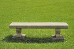 Stone bench on green field Stock Image