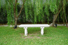 Stone bench on green grass Stock Photography