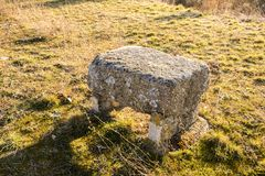 Stone bench. Lone stone bench over dead grass in a sunny winter day royalty free stock photo
