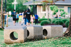Stone bench in the park with people are moving away in the backg Royalty Free Stock Photography