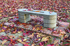 Stone bench and red leaves Stock Photos