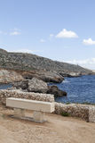 Stone bench on rocky coast of  Mediterranean Sea with blue water Royalty Free Stock Photo