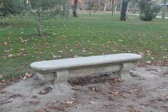 Stone bench surrounded by vegetationand sand royalty free stock photo