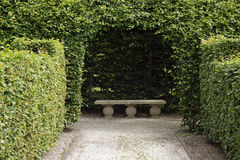 Stone bench under an arch. In a formal garden Royalty Free Stock Photos