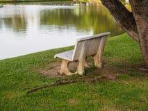 Stone bench under the tree near the pond stock photos