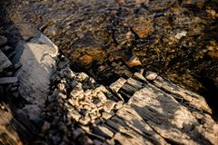Stone beneath serene river water. River water waves brushing through the stones fresh water stream in mountain brook, close up stock image