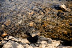 Stone beneath serene river water. River water waves brushing through the stones fresh water stream in mountain brook, close up stock photo