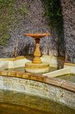 Stone birdbath in garden. Classical Stone birdbath in garden near wall Royalty Free Stock Image