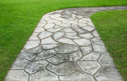 The Stone block walk path in the park with green grass Royalty Free Stock Photos