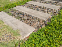 Stone block walk way in garden with green grass and rocks Royalty Free Stock Image