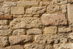 Stone block wall texture of a medieval building. Stone block wall texture on a old medieval wall viewed head on stock photo