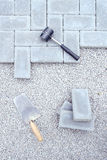 Stone blocks for paving laying down background with hammer and trowel Stock Photography