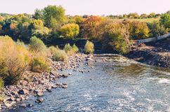 Stone blocks in a river surrounded by trees royalty free stock images
