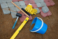 Stone blocks rubber hammer level gloves and tape measure. Pavement details, stone blocks rubber hammer level gloves and tape measure Stock Images