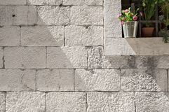 Stone blocks wall with detail of flower decorated window. Detail of flower decorated window on stone made facade of old house in medieval town stock photo