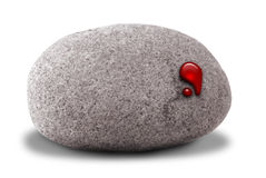 Stone with blood droplet on it. A small stone with a drop of blood coming out of it representing the idiom, getting blood out of a stone. Isolated on a white Royalty Free Stock Photos