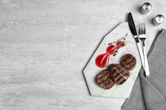 Stone board with grilled meat and sauce on light background, top view. Space for text royalty free stock photography