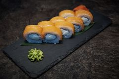 On a stone board of slate lie the sushi rolls. On a bamboo sheet with wasabi Royalty Free Stock Photos