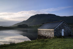 Stone boat shed and mountain reflected in lake at sunrise Stock Photos