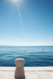 Stone bollard on boat dock and sea Stock Image