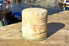 Stone bollard and a mooring rope royalty free stock photos