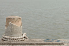 Stone bollard with rope on boat dock and sea Royalty Free Stock Image