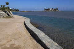 Stone border on the sea and the island. Stock Image
