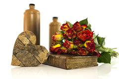 Stone bottle with old book and red roses Stock Photography