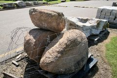 Stone Boulders for Patio Projects. Round Stone Boulders on pallets ready for delivery to homes for new home construction and patio projects Stock Photos