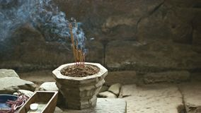 Stone bowl with incense sticks in the room of the ancient temple stock video footage