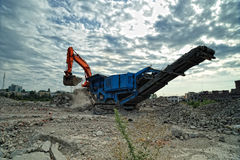 Stone breaker loading by an orange excavator Royalty Free Stock Photography