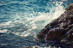Stone breakwater with breaking waves. Stock Image