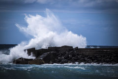 Stone breakwater with breaking waves. Royalty Free Stock Image
