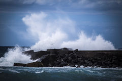 Stone breakwater with breaking waves. Royalty Free Stock Photo