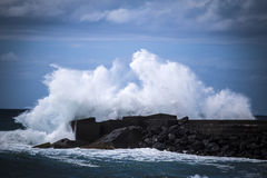 Stone breakwater with breaking waves. Stock Photography