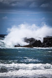 Stone breakwater with breaking waves. Royalty Free Stock Images