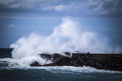 Stone breakwater with breaking waves. Stock Photo