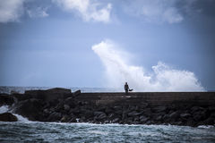 Stone breakwater with breaking waves. Royalty Free Stock Photos
