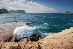 Stone breakwater with breaking waves Royalty Free Stock Photography