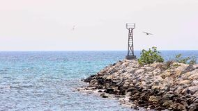 Stone breakwater and construction for blue sea navigation, seagulls flying, Halkidiki Greece. Stone breakwater and construction for blue sea navigation, seagulls stock footage