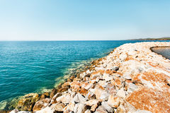 Stone breakwater in harbor in Greece Royalty Free Stock Photo