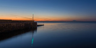 Stone breakwater at sunset. A stone breakwater, in a very calm sea, at sunset, with a green warning light, reflecting in the sea Stock Photo